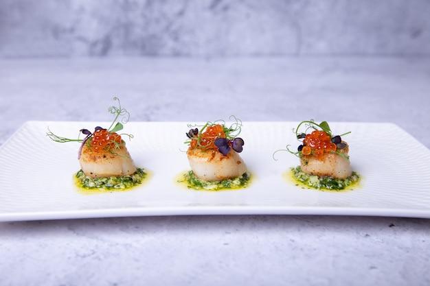 Морские гребешки с микрозеленью икры и зеленым соусом на белой тарелке
