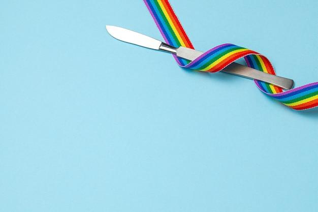 메스와 무지개 lgbt 리본 자부심 상징 성전환 수술 파란색 배경 복사 공간