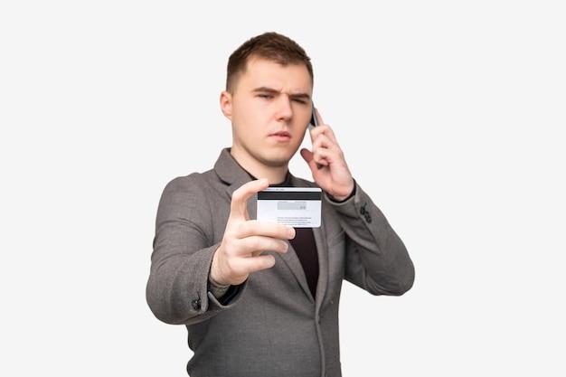 사기전화. 피싱 공격. 흰색 절연 신용 카드 개인 데이터를 말하는 혼란된 남성 은행 클라이언트.