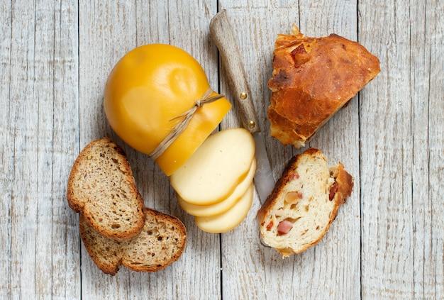 スカモルツァ、典型的なイタリアのスモークチーズと木製のテーブルの自家製パン