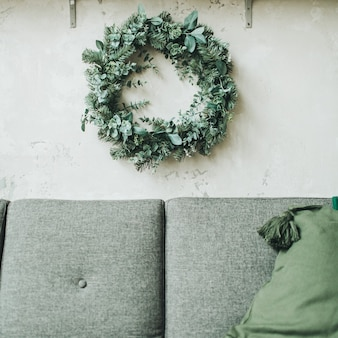 Scandinavian apartment decorated with christmas wreath made of fir and eucalyptus, grey couch with pillows
