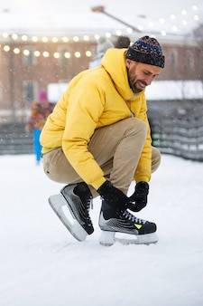 Scandinavian bearded man tying black skates on ice rink in snowy winter day