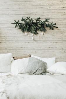 モミの枝と白いおもちゃで作られたクリスマスの装飾が施された白いリネンのスカンジナビアのベッドルーム