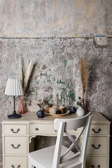 콘크리트 벽에 마른 허브, 램프, 양초 및 화환으로 만든 아늑한 집을위한 스칸디나비아 장식 말린 꽃과 현대적인 인테리어에 식물. 에코 스타일의 인테리어 장식