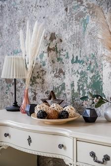 コンクリートの壁に乾燥したハーブ、ランプ、キャンドル、花輪をあしらった居心地の良い家のスカンジナビア風の装飾。エレガントなパーソナルアクセサリーや植物。家の装飾。エコスタイル
