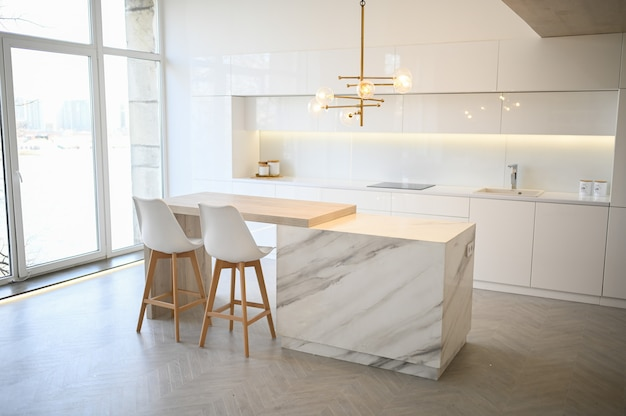北欧の空の古典的なモダンで豪華なキッチンには、木製、白、大理石のディテール、新しいスタイリッシュな家具、ミニマルな北欧のインテリアデザインが施されています。バースツール