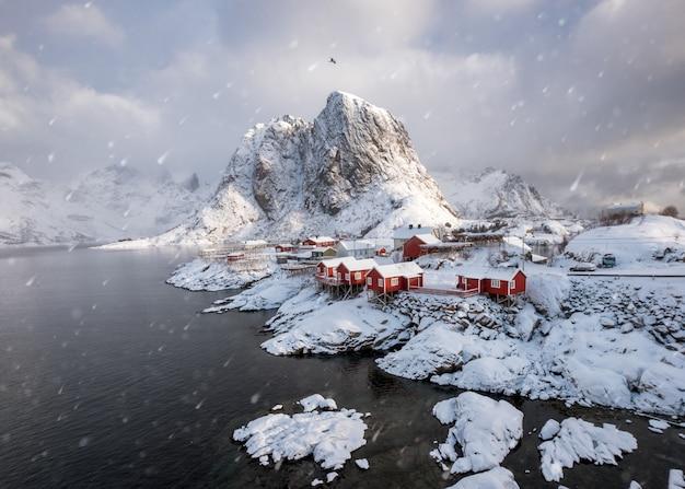 Scandinavian fishing village in snowfall on coastline at hamnoy