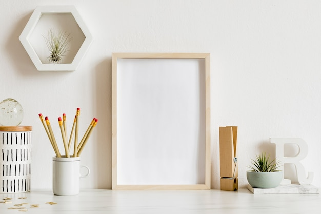 Scandinavian home office interior with wooden mock up poster frame, design office accessories, tapes, supplies, notes, memo sticks, air plants. minimalistic concept. template.