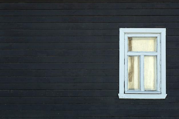스칸디나비아 집. 창으로 스칸디나비아 집 외관의 어두운 나무 벽.