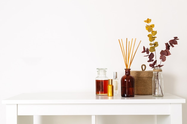 Scandinavian hygge style, home interior  aroma diffuser with wooden sticks, perfume, straw basket, dried eucalyptus branches