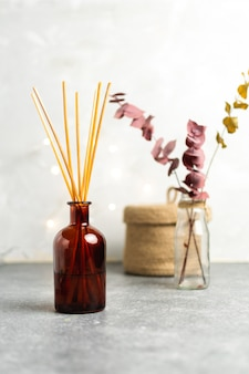 Scandinavian hygge style, home interior  aroma diffuser with wooden sticks, straw basket, dried eucalyptus branches