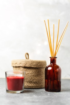 Scandinavian hygge style, home interior  scent aroma diffuser with wooden sticks, small straw basket, red candle,