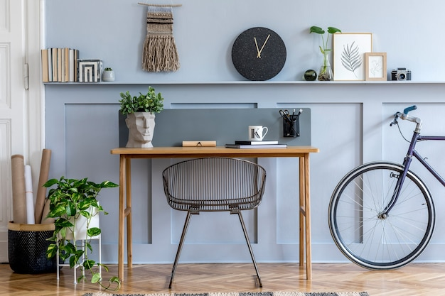 Scandinavian interior design of home office space with wooden desk, modern chair, wood paneling with shelf, plant, carpet, bicycle, office supplies and elegant personal accessories.