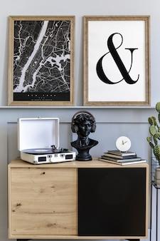 Скандинавский интерьер гостиной с макетом постера в рамке, виниловый диктофон и аксессуары