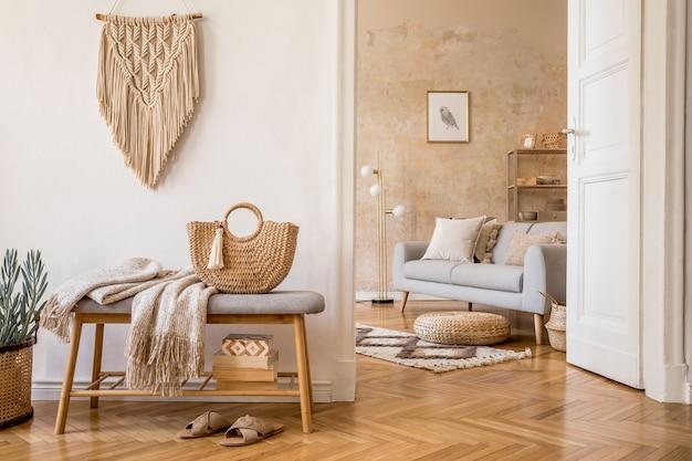 Скандинавский интерьер открытого пространства с деревянной скамейкой, серым диваном, подушками, палидом, макетной рамкой для фотографий, макраме, растением, книгами, ковром, украшениями и элегантными личными аксессуарами в домашнем декоре.