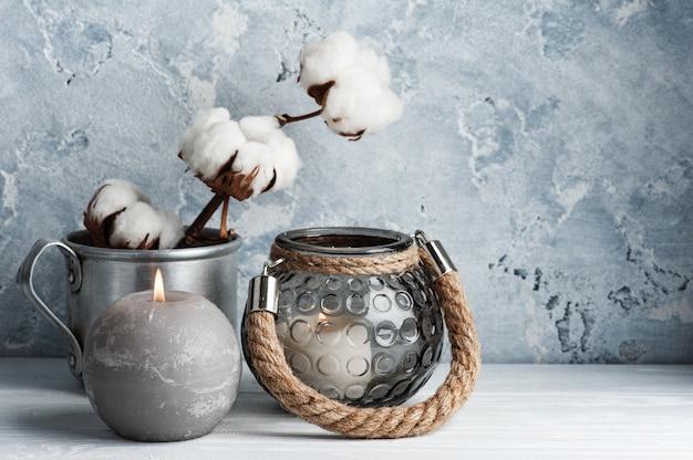 Скандинавский интерьер с цветами из хлопка и зажженными свечами в минималистской композиции.