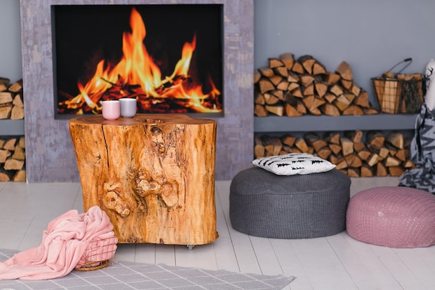 Scandinavian interior with a fireplace, stump table, a pile of logs for fire
