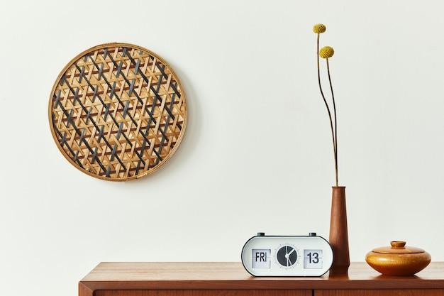 Скандинавский интерьер со стильным комодом из тикового дерева, дизайнерским декором из ротанга на стене, часами, засушенными цветами и элегантными личными аксессуарами. нейтральная гостиная в классическом доме. шаблон.