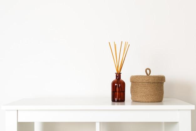 Скандинавский стиль нордической гигиены, домашний интерьер, ароматический диффузор с деревянными палочками, маленькая соломенная корзина, белая полка