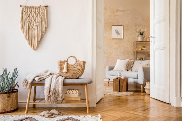 Интерьер в скандинавском стиле open space с деревянной скамейкой, серые подушки для дивана, клетчатая рамка для фотографий, макраме, растения, книги, украшение ковровой полки, и элегантные личные аксессуары в стильном домашнем декоре