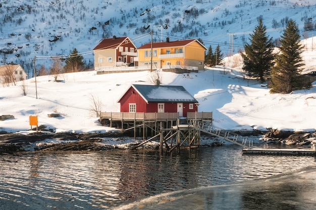 Scandinavian red house with wooden jetty on coastline