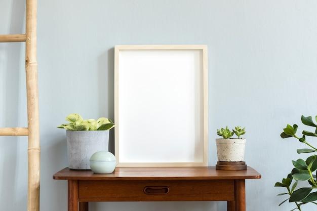 さまざまなヒップスターとデザインポットの美しい植物と茶色の竹の棚にフォトフレームとスカンジナビアの部屋のインテリア Premium写真