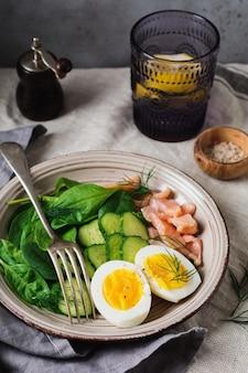 회색 세라믹 접시에 훈제 핑크 연어, 시금치, 오이, 닭고기 달걀을 넣은 스칸디나비아 샐러드
