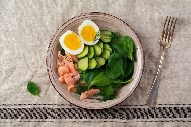 Scandinavian salad with smoked pink salmon, spinach, cucumber and chicken egg in gray ceramic dish. top view.