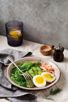 Scandinavian salad with smoked pink salmon, spinach, cucumber and chicken egg in gray ceramic dish.