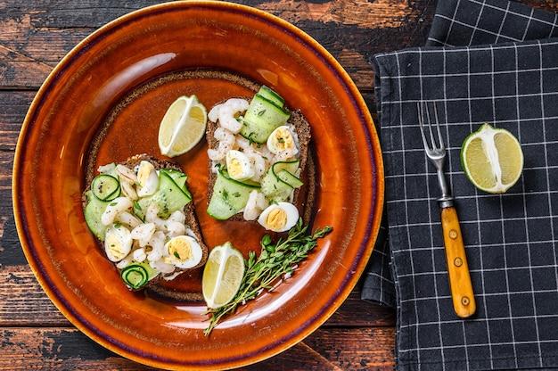 Скандинавские бутерброды с креветками, креветками, перепелиными яйцами и огурцом на ржаном хлебе. темный