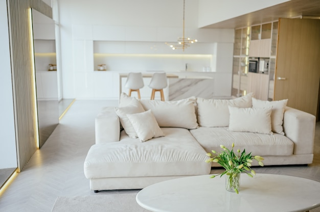 Scandinavian style bright classic modern luxury living dining room and kitchen with wooden, white, marble details, new stylish furniture, cozy sofa couch, minimalistic nordic interior design.