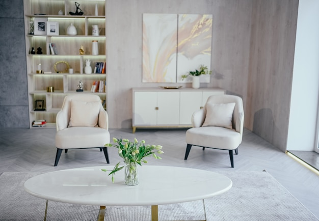 Scandinavian style bright classic modern luxury white living room with marble table, new stylish furniture, chest of drawers, cozy armchairs, indoor plants . minimalistic nordic interior design