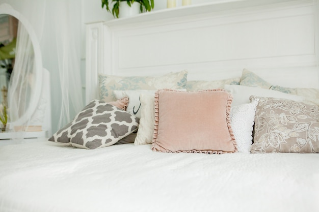 Белая спальня в скандинавском стиле. четыре подушки на кровати. современный интерьер