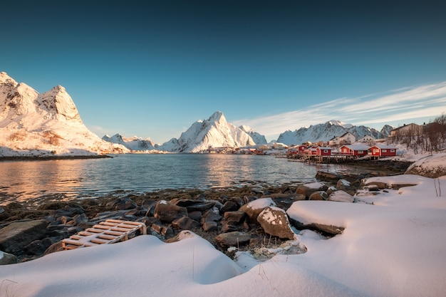 Scandinavian village in snowy mountain range on coastline