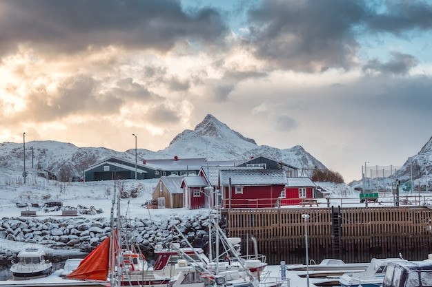 Scandinavian village with fishing boat and snow mountain in coastline