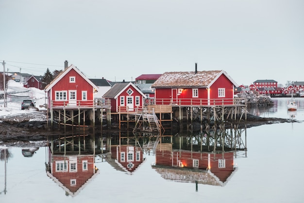 Scandinavian village with red house reflection on arctic ocean