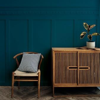 진한 파란색 벽으로 의자가있는 스칸디나비아 빈티지 나무 캐비닛