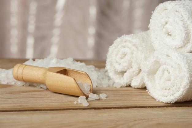 白いタオルの横にある木製のテーブルに海塩と肩甲骨