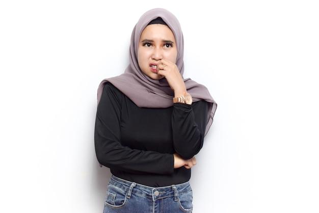 若い美しいイスラム教徒のアジアの女性の恐怖と神経質なジェスチャーと爪を噛む