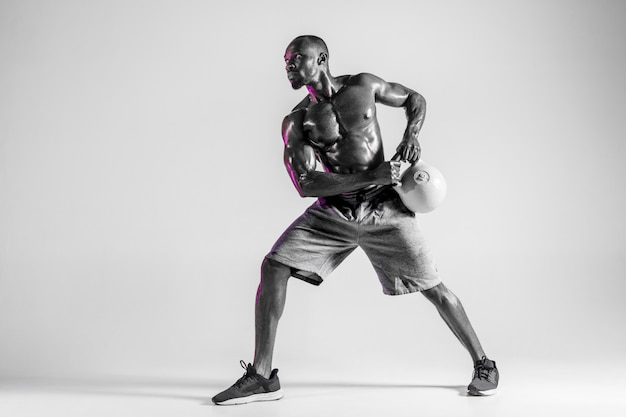 Don't scare. young african-american bodybuilder training over grey studio background. muscular single male model in sportwear with the weight. concept of sport, bodybuilding, healthy lifestyle.