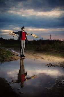 Scarecrow stands on country road by large puddle