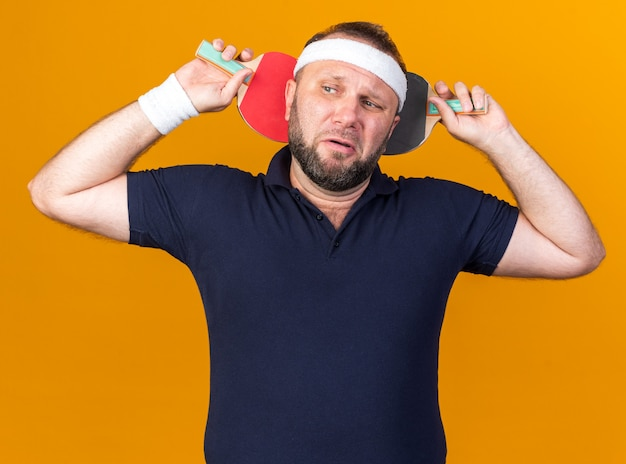 Scared adult slavic sporty man wearing headband and wristbands holding table tennis rackets behind his head looking at side isolated on orange wall with copy space