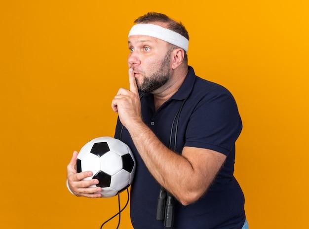 Испуганный взрослый славянский спортивный мужчина со скакалкой на шее в головной повязке и браслетах держит мяч и делает жест молчания, изолированный на оранжевой стене с копией пространства