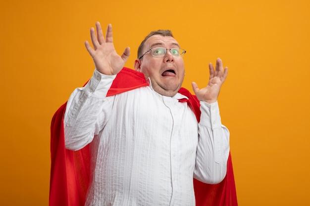 Испуганный взрослый славянский супергерой в красном плаще в очках, держа руки в воздухе, глядя вверх изолирован на оранжевом фоне с копией пространства