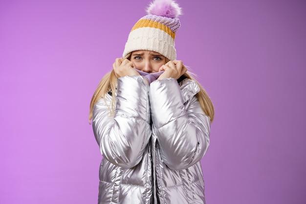 かわいい帽子をかぶった怖い不安な臆病な女の子きらびやかな光沢のあるジャケットプル布の顔おびえた眉をひそめている身をかがめる表情心配怖い怖い死、立っている紫色の背景臆病。