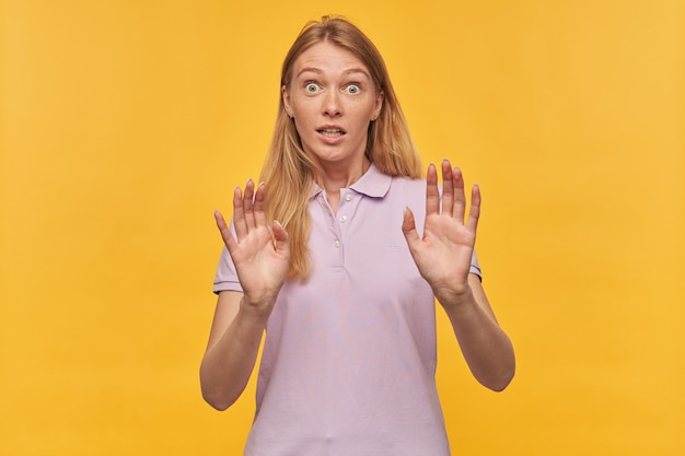 Scared afraid woman with freckles in lavender tshirt keeps hands on front of herself and defending from enemies on yellow