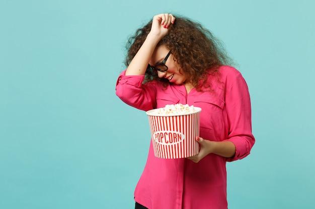 3d 아이맥스 안경을 쓴 겁에 질린 아프리카 소녀가 푸른 청록색 벽 배경에 격리된 손으로 팝콘을 덮고 영화 영화를 보고 있습니다. 영화, 라이프 스타일 개념에서 사람들의 감정. 복사 공간을 비웃습니다.