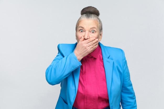 Испуганная пожилая женщина закрыла рот и большие глаза