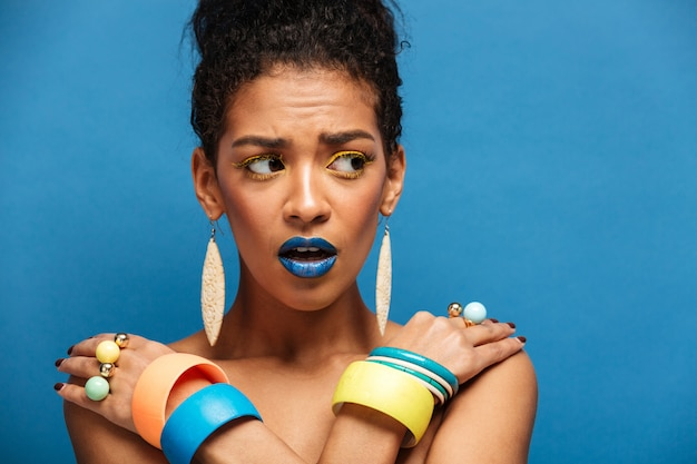 Scared or agitated mulatto woman with colorful makeup and fashion accessories looking aside with crossed hands on shoulders, over blue wall