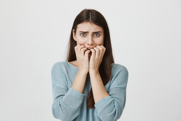 Scared alarmed woman biting fingernails, frowning frightened